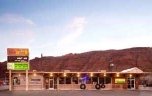 image of store front in moab utah with red rocks behind it