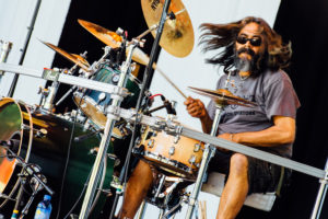 man playing drums at concert with long hair
