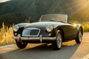 picture of MG black car in mountain setting with sun setting behind it