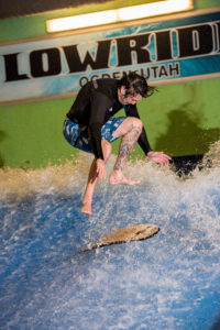 Marketing, man surfing in an indoor wave pool