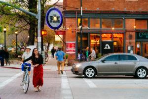 girl walking a bike across a street in front of a restaurant