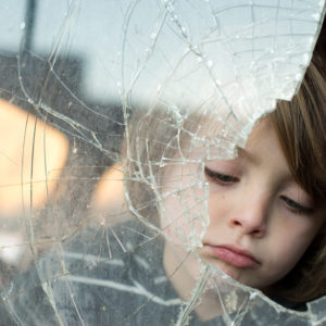 Photography, image of boy looking through broken glass