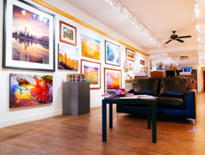 marketing, image of a gallery inside with landscape pictures on the wall and black leather couch