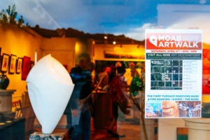 Picture of a white sculpture through a gallery window with poster