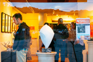 Picture of sculpture in a window of a gallery with people inside