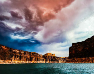 Landscape, picture of lake with cliffs around the edge purple rainy sky