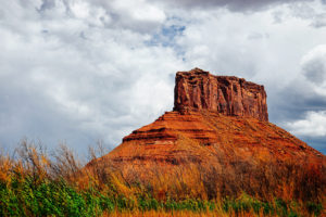 landscape, Picture of red cliffs with grass in front of it.