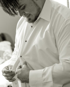 Wedding, Moss Image, Moab Photographer, Portrait, Chris Moss, black and white photo of man buttoning up his shirt while looking down
