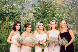Moss Image, Bride and bridesmaids holding flowers with trees in the background