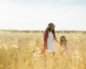 mother and daughter holding hands in a field wile looking down, yellow grass, blue sky