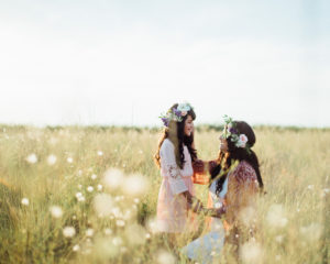 mother and daughter looking at each other in a field of flowers