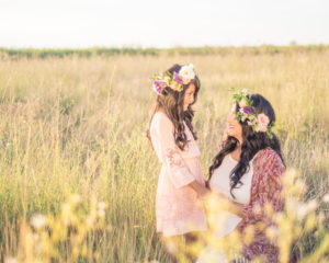 mother and daughter looking at each other in a field