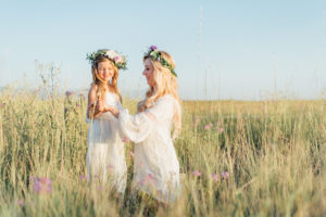 mother and daughter in white dresses with flowers in their hair wile in a field