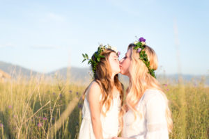 mother and daughter kissing with flowers in their hair with flowers in the background