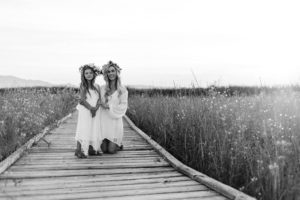 Black and White photo with mom holding daughter in white dress with field of flowers in the background