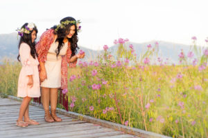 Little girl and her mom looking at purple flowers with mountains in the background