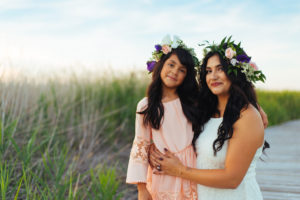 Mom holding daughter with flowers in their hair, blue sky in the background with green grass