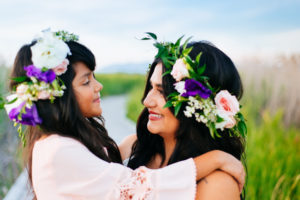 Portrait, Moss iMage, Moab Photographer, Mother and daughter smiling at each other with purple and pink flowers in their hair and blue sky in the background