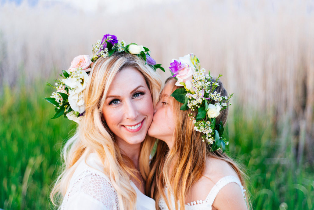 Portrait, CHris Moss, Moss Image, girl kissing her mom on the cheek with flowers in their hair and green grass in the background