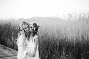 black and white photo with daughter kissing mothers cheek with tall grass in background