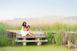 mom in white dress holding her child while sitting next to a pond