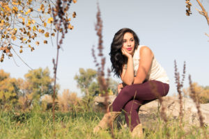 girl in red pants sitting on a log in a field blue sky in the background