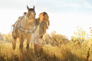 Portrait, Moss Image, Moab Photographer, Girl wearing a blue jean shirt and white dress holding her horse and standing in a field