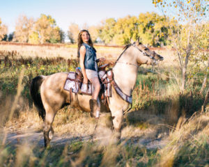 Girl wearing a blue jean shirt and white skirt riding her horse with a field in the background