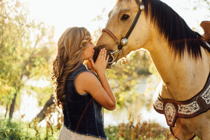 Portrait, Moss Image, Girl in a blue jean shirt kissing her horse on the nose