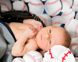baby sitting in a baseball glove surrounded by baseballs