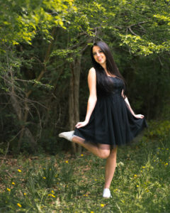 Girl in a black dress standing in a field with green trees in background