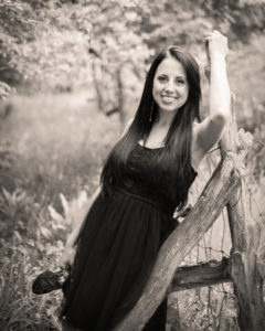 Black and white photo of girl in black dress leaning against a wooden fence post with trees in the background