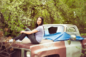 girl wearing a blue shirt and jeans while sitting on the hood of an old truck with a broken window