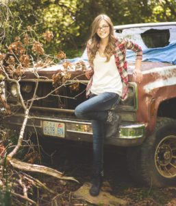 girl resting against the front of an old truck with a broken window wearing blue jeans and a white shirt