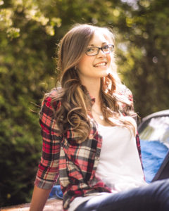 Portrait, girl in a red plaid shirt wearing glasses and sitting with green trees in the background