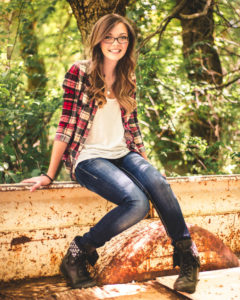 Moab, Portrait, Photo, chris moss, Girl sitting in the bed of an old truck wearing blue jeans and a red plaid shirt with trees in the background