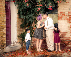 Mom and Dad standing in front of a brick wall with flowers above while kissing and their kids are watching them