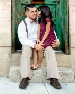 Father in white shirt holding daughter while she is kissing his cheek in front of a green door