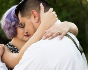 picture of a man holding a woman with the woman's arms wrapped around the mans neck displaying her new wedding ring