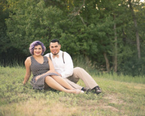 Wedding, Moss Image, Moab Photographer, Portrait, Chris Moss, picture of a man and woman holding each other sitting in a field with green trees in the background