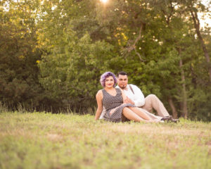 Picture of a man and woman dressed in fifties style clothing sitting in a field looking at the camera green trees in the background
