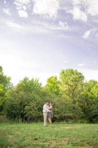 picture of a man and woman holding each other with green grass and trees and a blue sky in the background