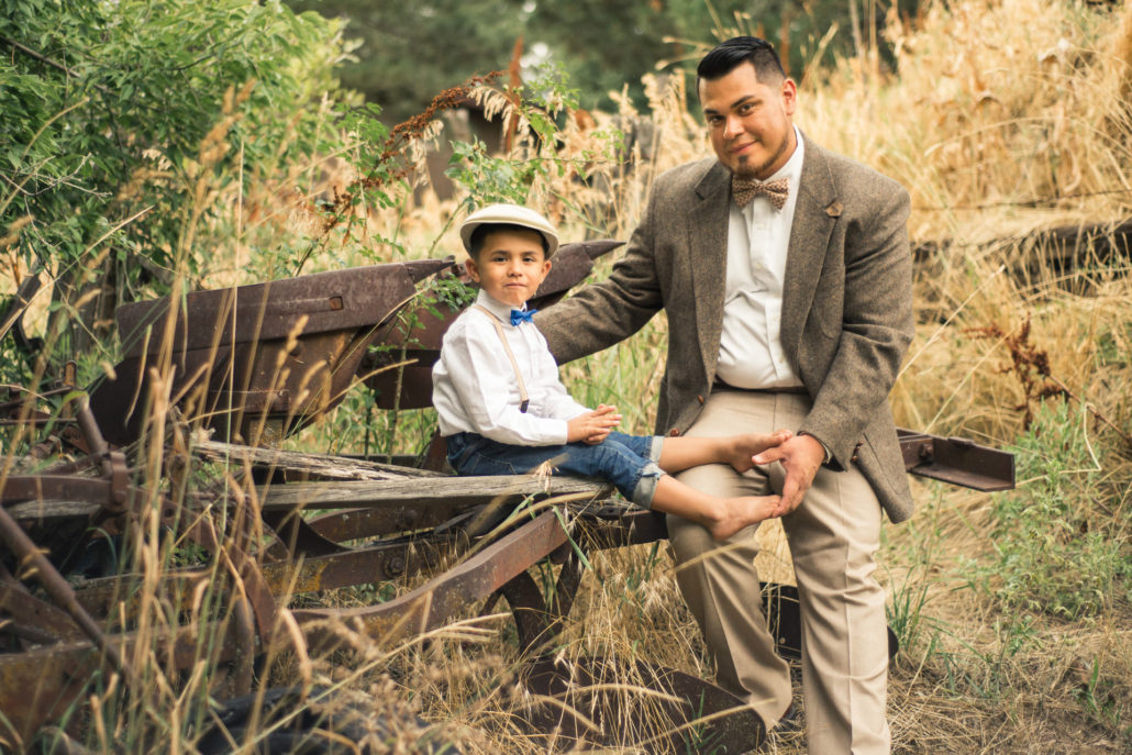 Location Photography, picture of a father and son in fifties style clothing sitting on old machinery looking at the camera