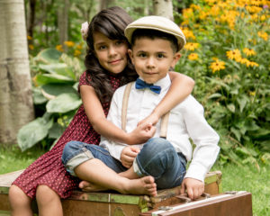 Picture of a sister and a brother dressed up in fifties style clothing while sitting on a box
