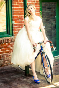 Picture of a bride in her wedding dress riding on a blue bicycle wearing blue high heels with green door in the background