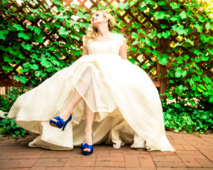 Picture of a bride in her wedding dress showing off her blue shoes while looking away from the camera