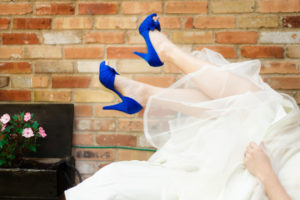 Picture of a bride showing off her blue high heel shoes with a brick wall in the background