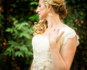 Portraits, Picture of a bride in her wedding dress looking away from the camera showing off her wedding ring