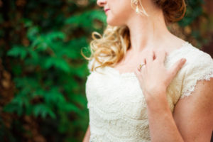 Picture of a bride in her wedding dress resting her hand on her chest displaying her wedding ring