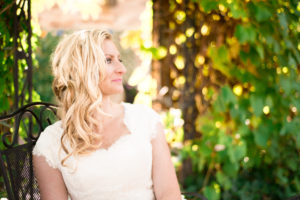 Picture of a bride in her wedding dress sitting in a chair and looking away from the camera with green foliage in the background